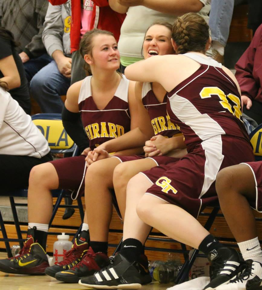 Macahla Leslie hugs teammate Megan Gray while Jacey Murphy shares in what would soon be a celebration. PHOTO BY AMY GRAY